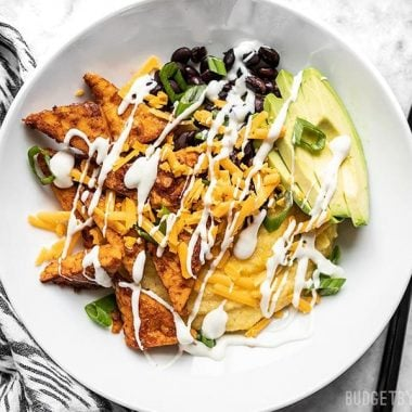 A prepared Sweet and Spicy Tempeh Bowl with ranch drizzle.