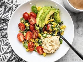 A large bowl of Vegetable Breakfast Scrambles about to be eaten with a fork.