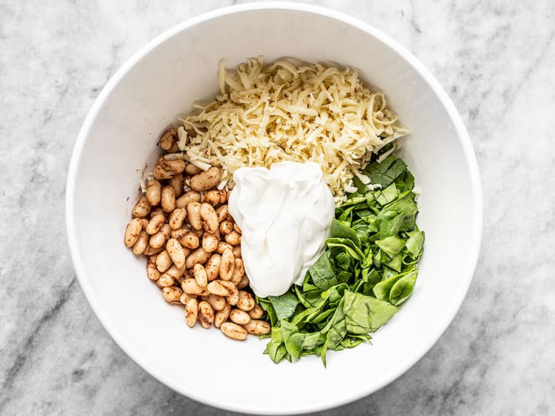 Beans, spinach, cheese, and sour cream in a bowl