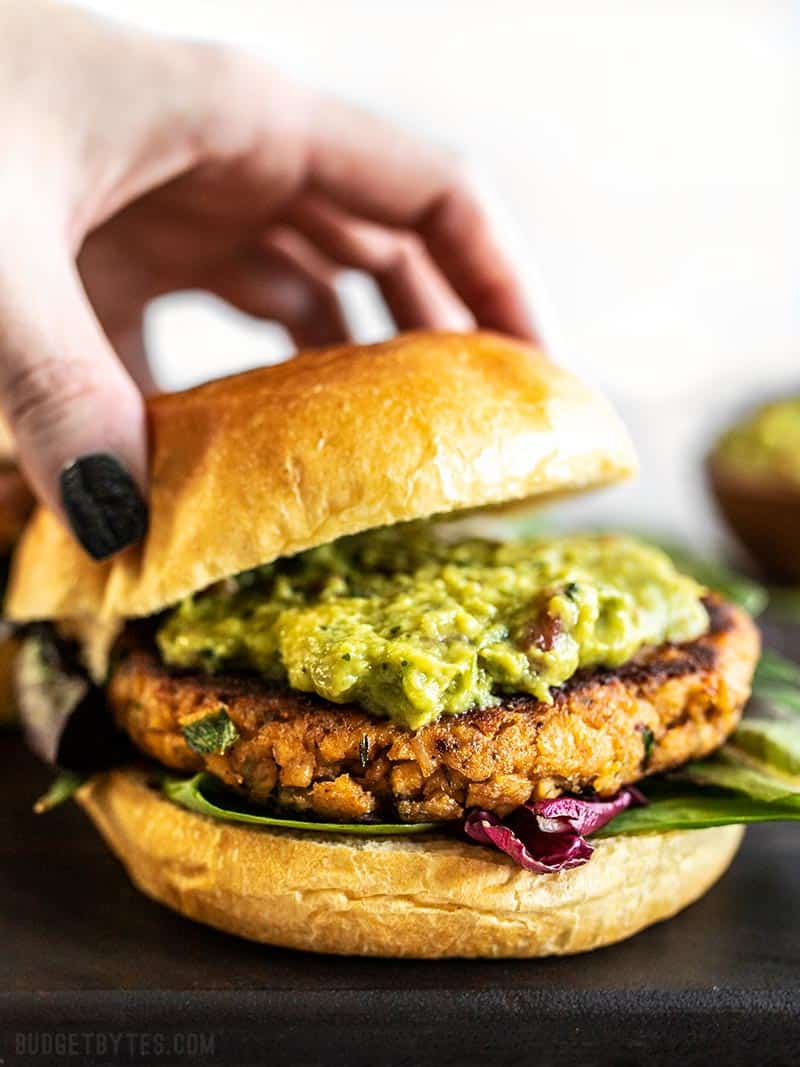 A Cajun Salmon Burger with guacamole being topped with the top half of a bun