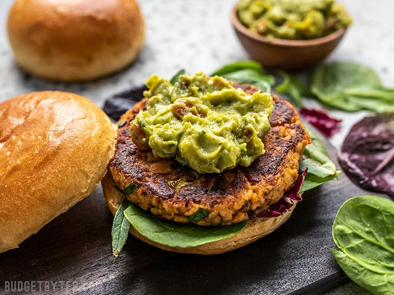 A Cajun Salmon Burger topped with guacamole without the top bun.