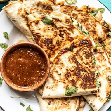 Close up of a plate full of creamy white bean and spinach quesadillas with a dish of red salsa