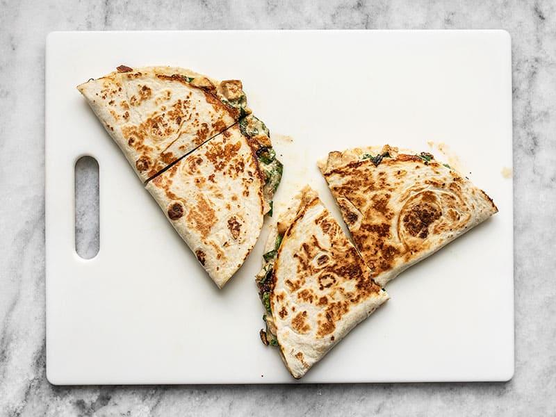 Quesadillas on a cutting board, cut in half