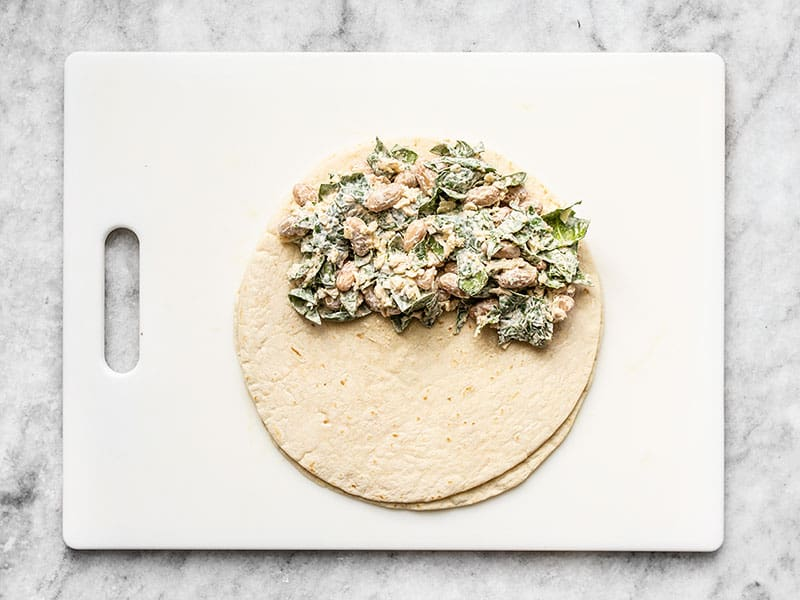 Flour tortilla with spinach and bean mixture covering half