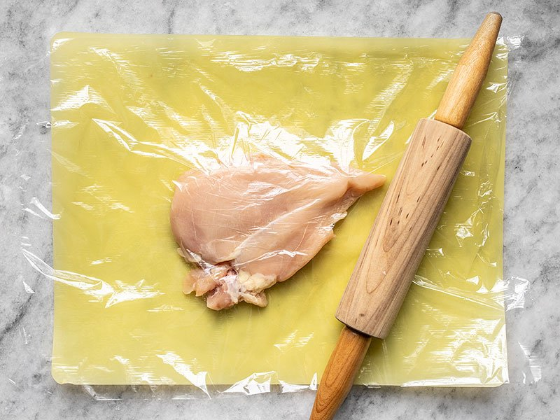 Chicken Breast covered in plastic wrap being pounded with a rolling pin