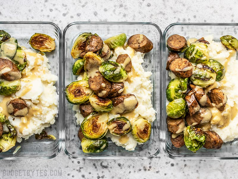Three glass meal prep containers full of Roasted Brussels Sprout Bowls lined up.