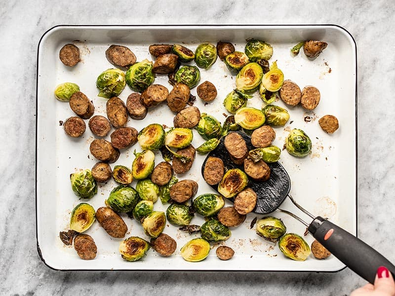 Roasted Brussels Sprouts and Sausage on the baking sheet with a spatula