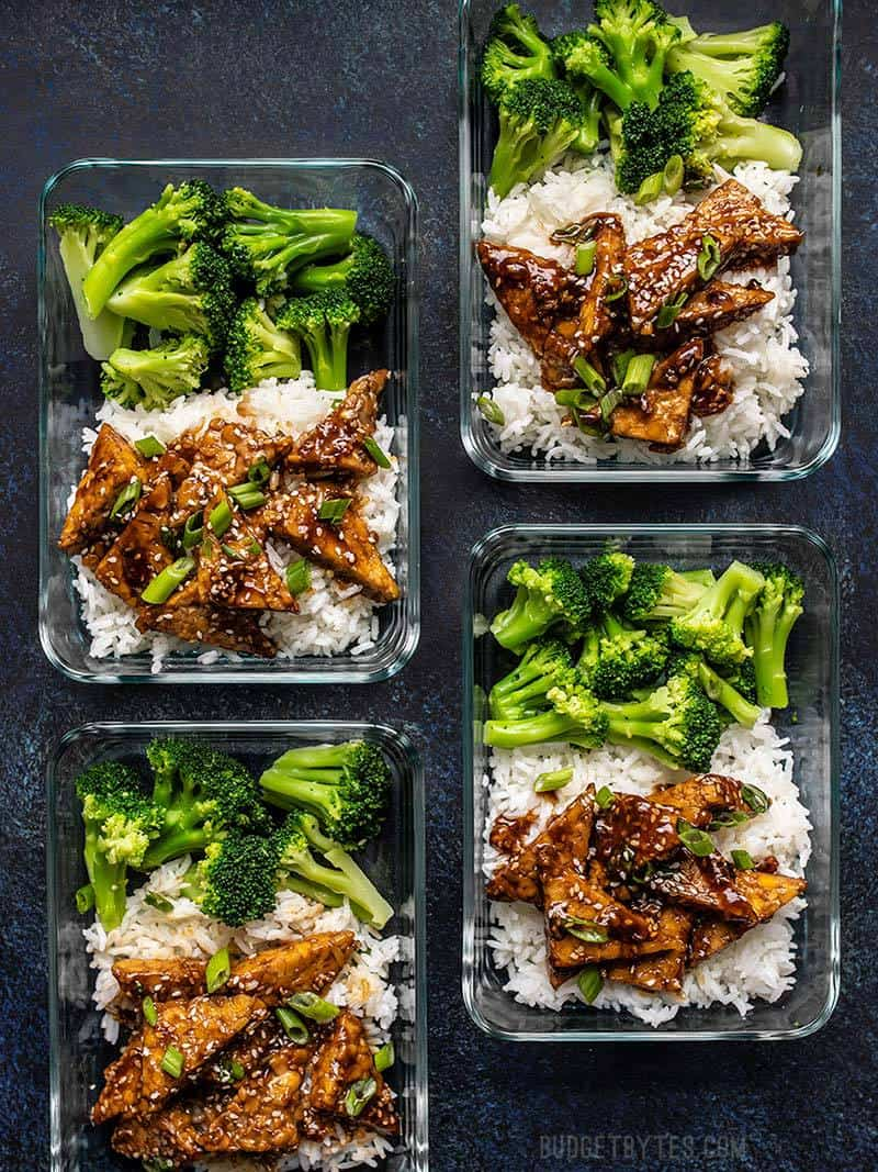 Four glass meal prep containers full of Sesame Tempeh Bowls