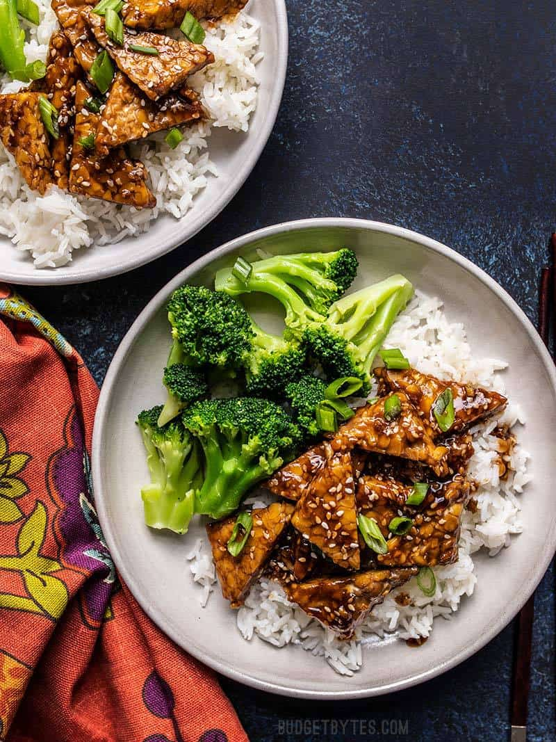 Two plates with Sesame Tempeh, rice, and broccoli, next to a colorful napkin