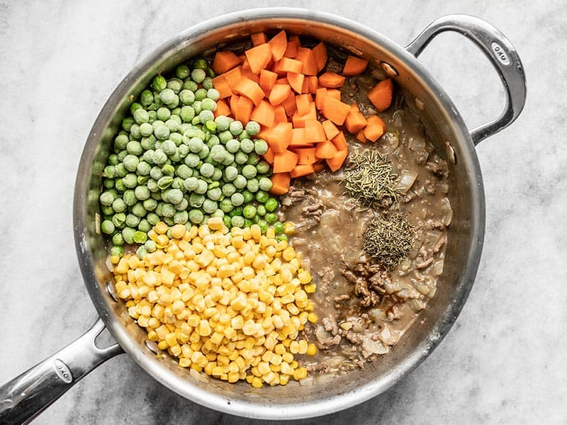 Add Vegetables Herbs and Spices to Beef and Gravy in the skillet