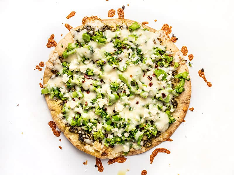 Baked Broccoli Pesto Pizza on the baking sheet with browned cheese around the edges.