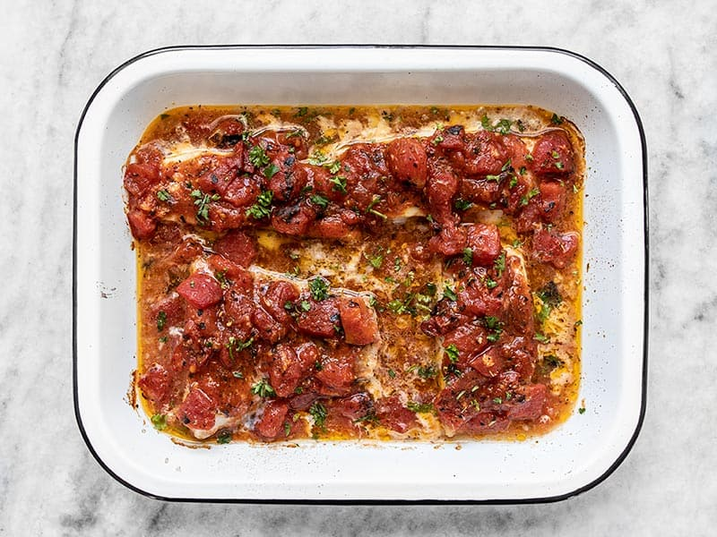 Baked fish with tomatoes in the baking dish