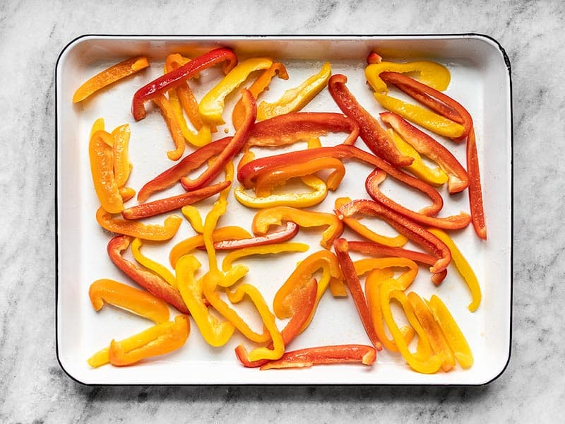 Sliced Bell Peppers on baking sheet, coated in oil