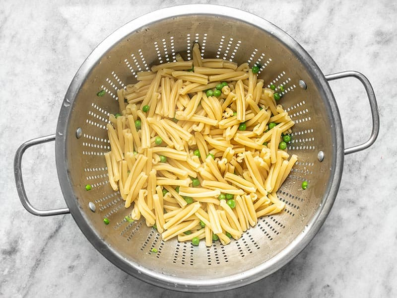 Boiled Pasta and Peas draining in a metal colander