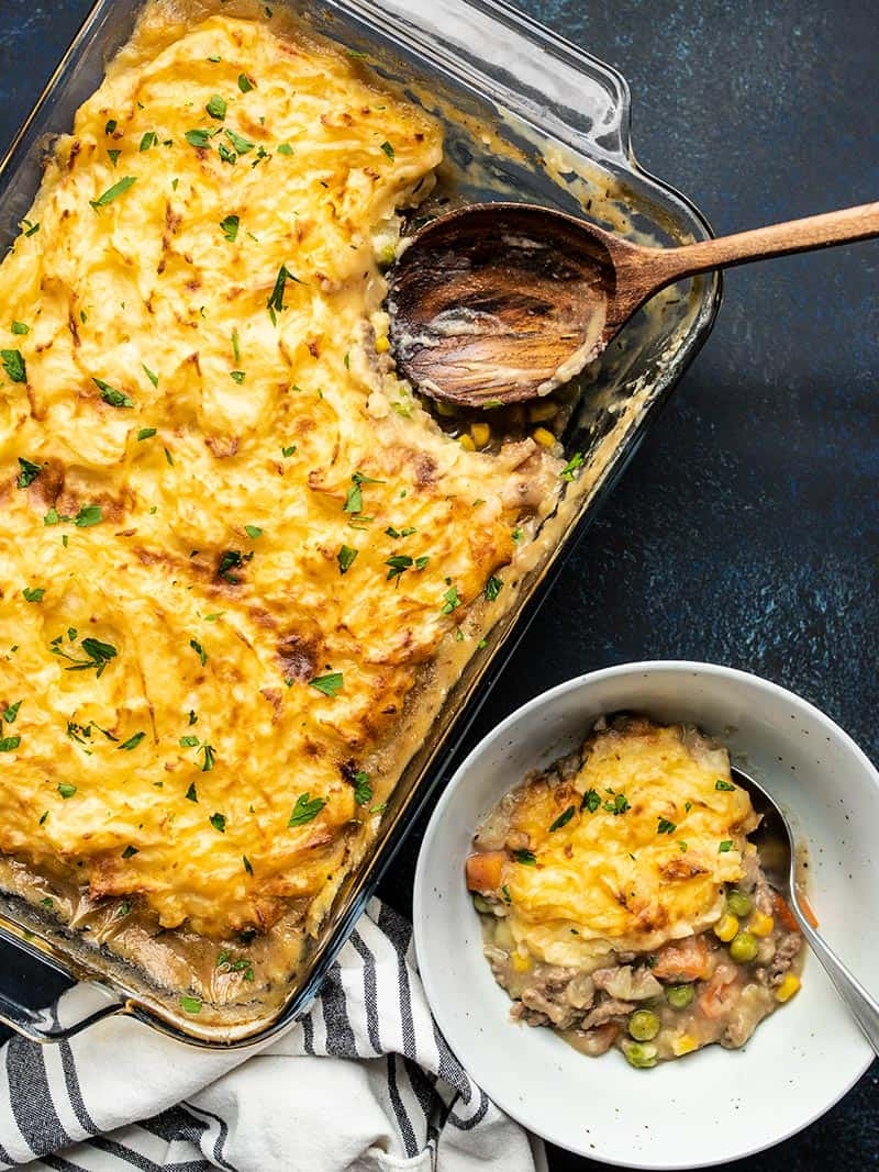 A casserole dish full of Cheesy Cottage Pie with a portion scooped out into a bowl on the side