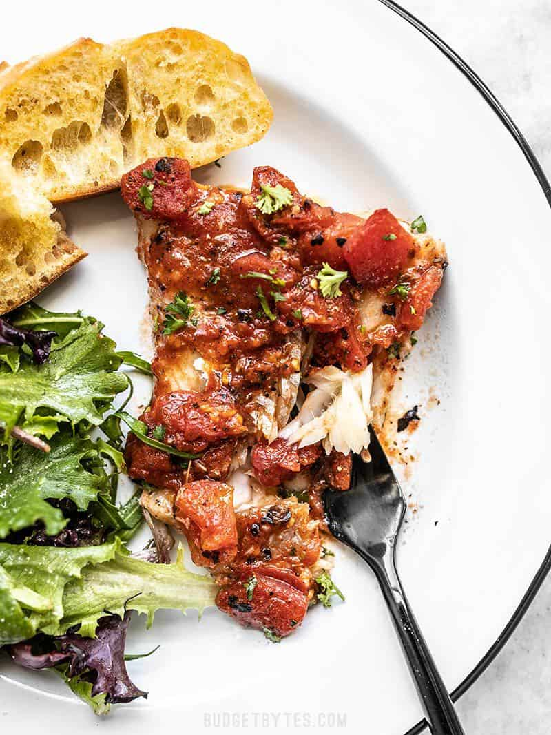 A piece of Easy Oven Baked Fish with Tomatoes on a plate with baguette slices, a green salad, and black fork