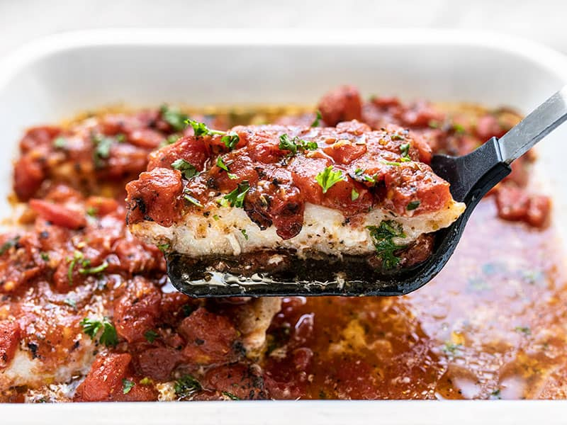 A fillet of baked fish with tomatoes being lifted out of the baking dish with a spatula