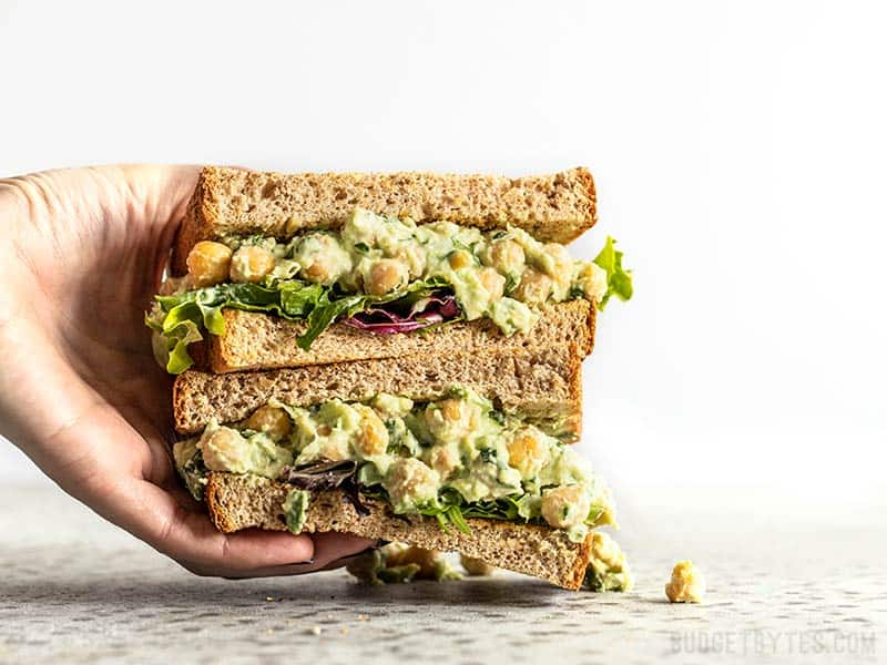 A hand grabbing a stack of two halves of a Scallion Herb Chickpea Salad sandwich on wheat bread.