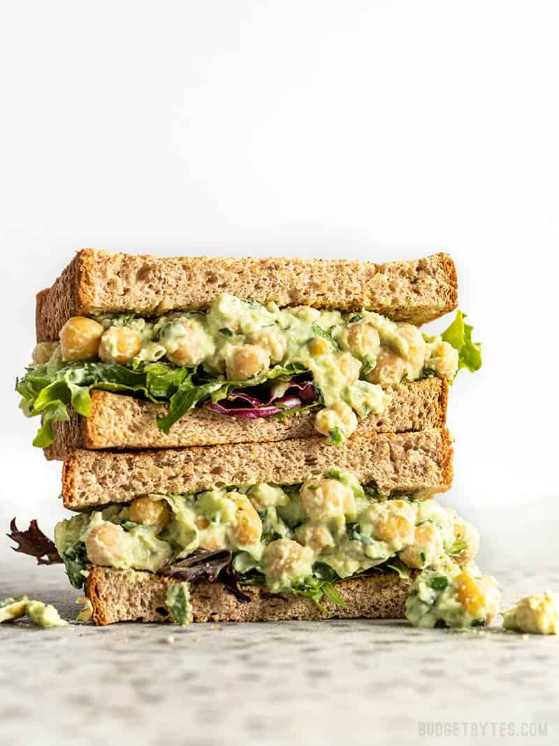 Two stacked halves of a Scallion Herb Chickpea Salad sandwich on wheat bread.