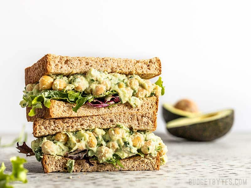 Two halves of a Scallion Herb Chickpea Salad sandwich on wheat bread, stacked. An avocado in the background.