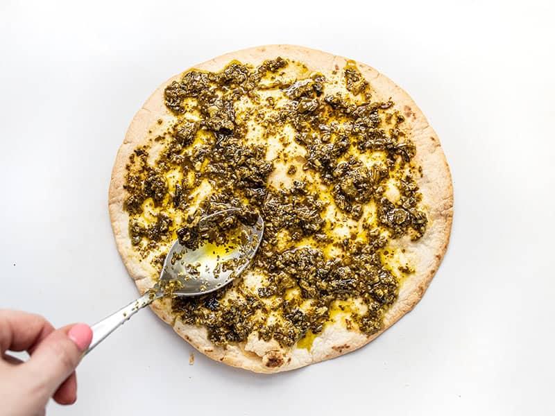 Spread Pesto on the par-baked tortilla