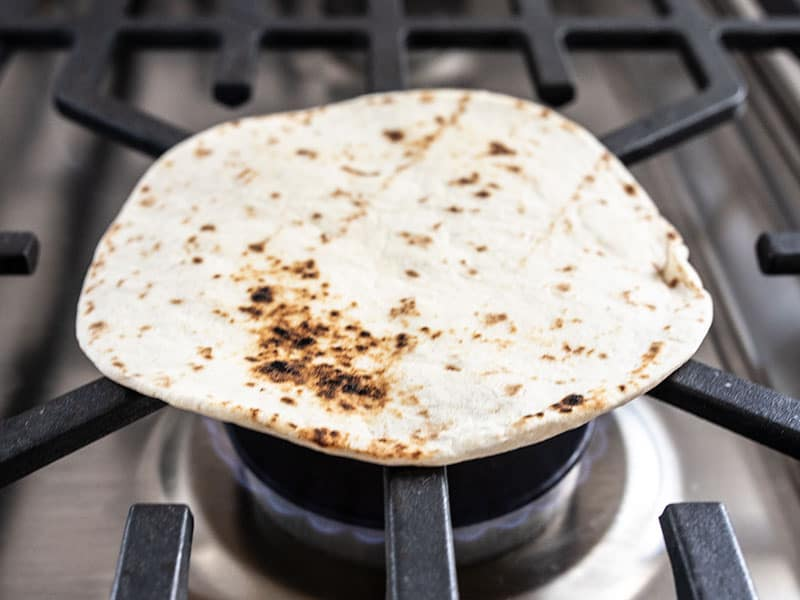 A flour tortilla being toasted over an open gas flame