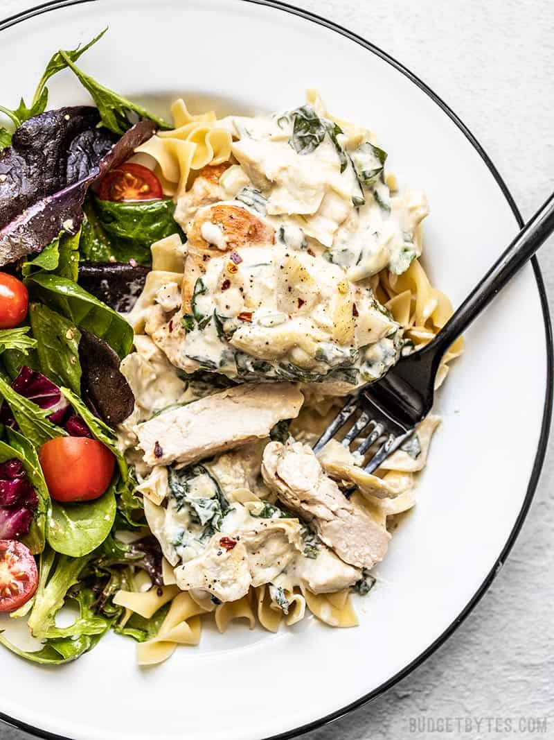 Creamy Spinach Artichoke Chicken on a plate with a bed of pasta and a salad on the side