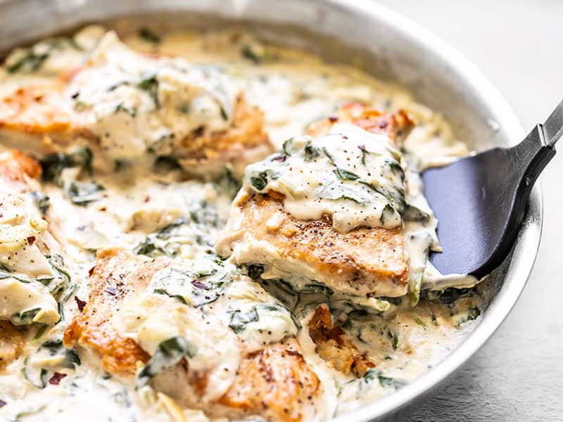 A piece of Creamy Spinach Artichoke Chicken being lifted out of the skillet with a spatula, side view