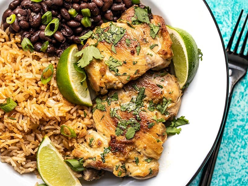 Easy Cilantro Lime Chicken on a plate with black beans and taco rice
