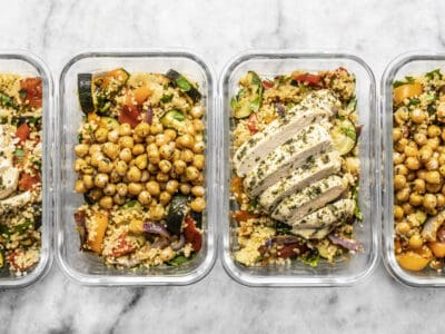 Four glass meal prep containers lined up with roasted vegetable couscous. Two with chicken and two with chickpeas