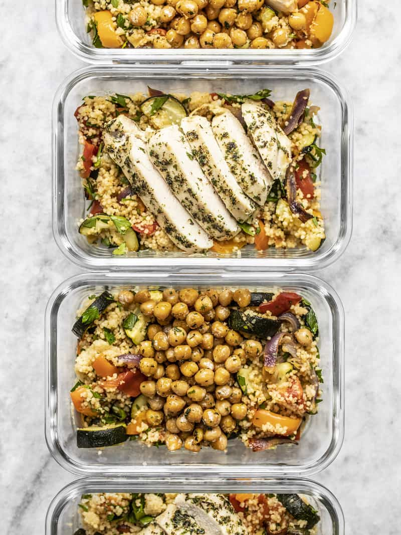 Four glass meal prep containers lined up with Roasted Vegetable Couscous and Garlic Herb Baked Chicken or Garlic Herb Chickpeas