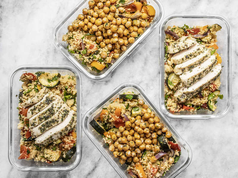 Four glass meal prep containers with roasted vegetable couscous, two with sliced chicken breast, two with garlic herb chickpeas