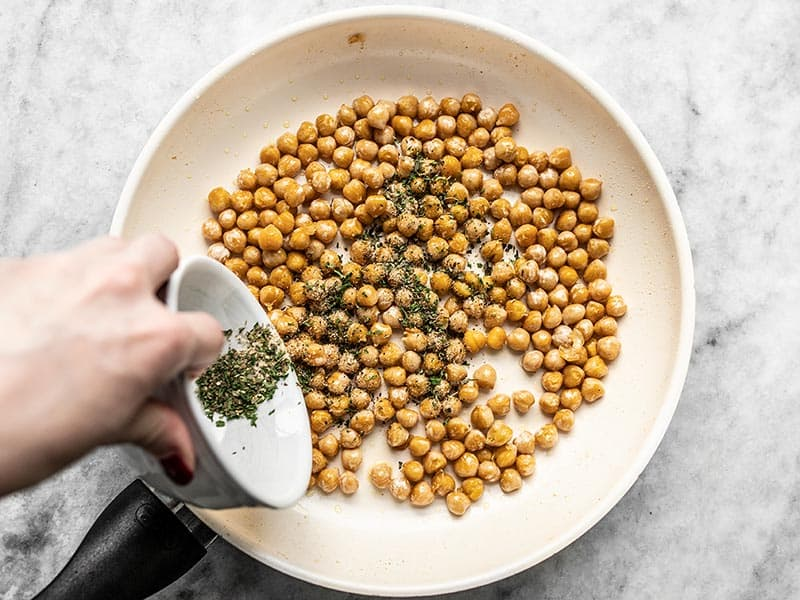 Season Chickpeas in skillet with garlic herb seasoning.