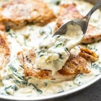 Creamy Spinach Artichoke Sauce being spooned over a piece of browned chicken