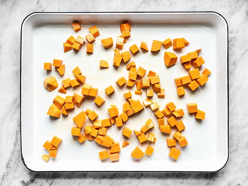 Cubed sweet potatoes on a baking sheet, coated in oil, and ready to be roasted.