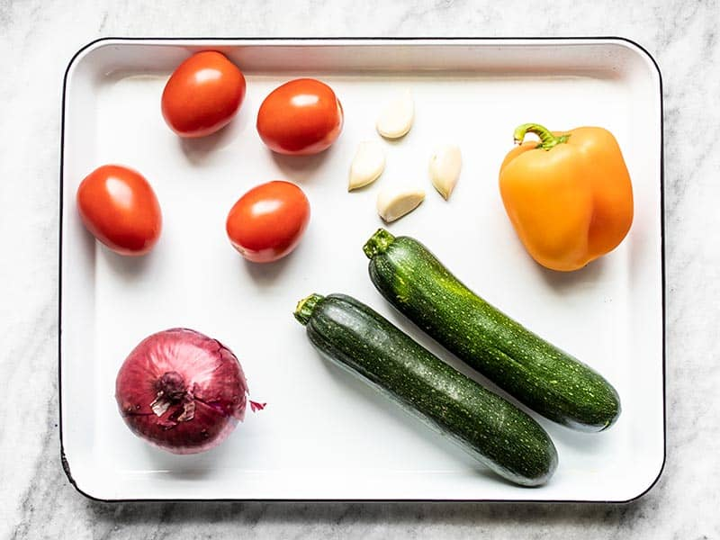 Whole vegetables for roasted vegetable couscous, on baking sheet