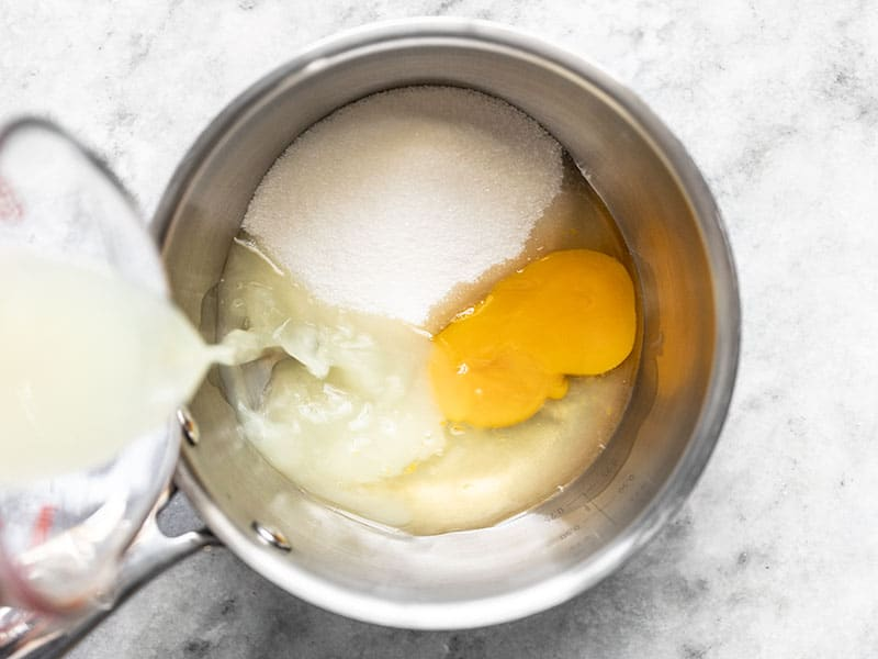 Lemon juice being poured into a sauce pot with sugar and an egg.