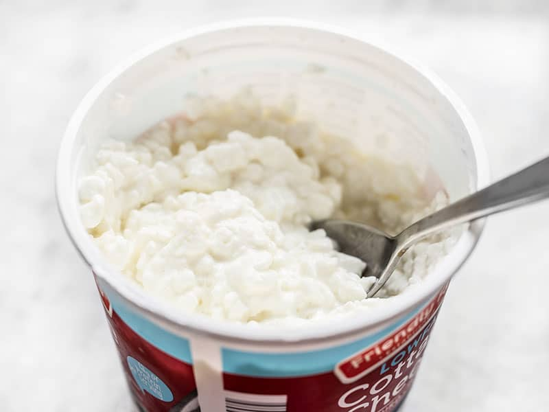 Cottage cheese container with a spoon in it