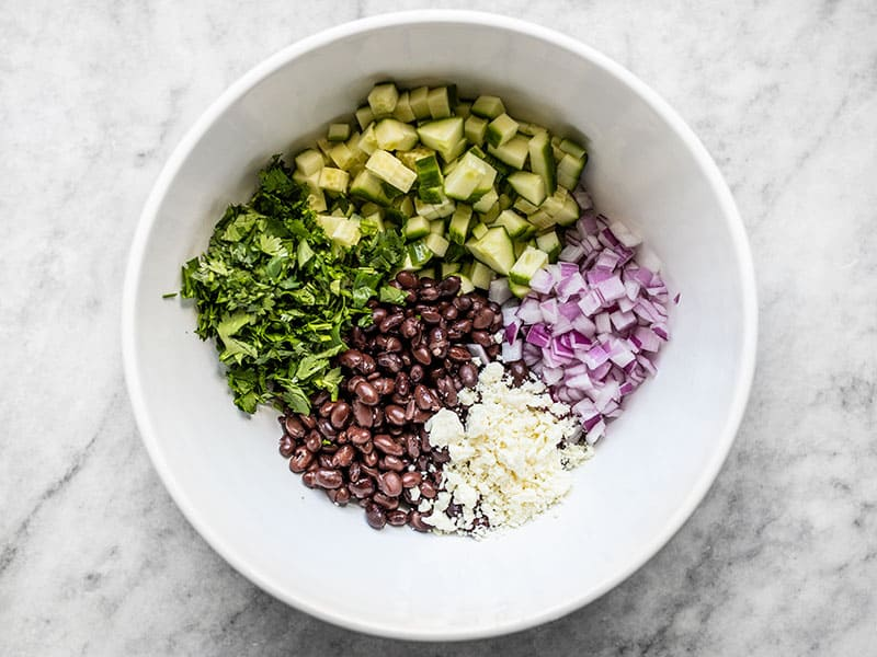 Cucumber and Black Bean Salad ingredients in a white bowl
