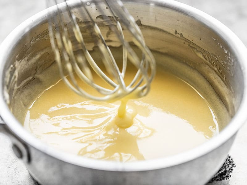 Finished lemon curd dripping off the whisk into the sauce pot.