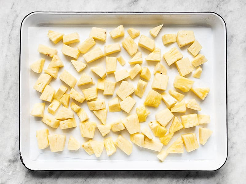 Fresh pineapple chunks spread out on a parchment lined baking sheet.