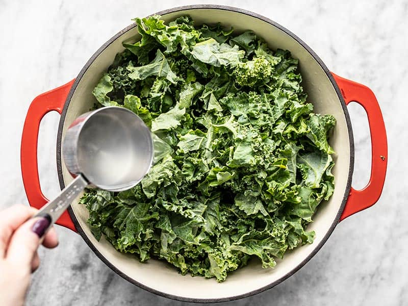 Fresh kale in the pot with pasta water being poured over top.