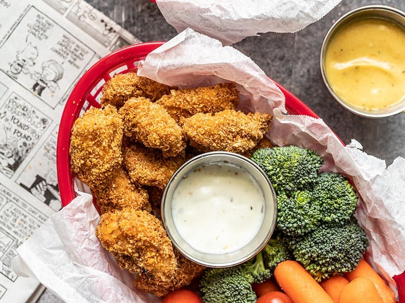 A basket full of Homemade Baked Chicken Nuggets, broccoli, carrots, tomatoes, and a small dish of ranch.