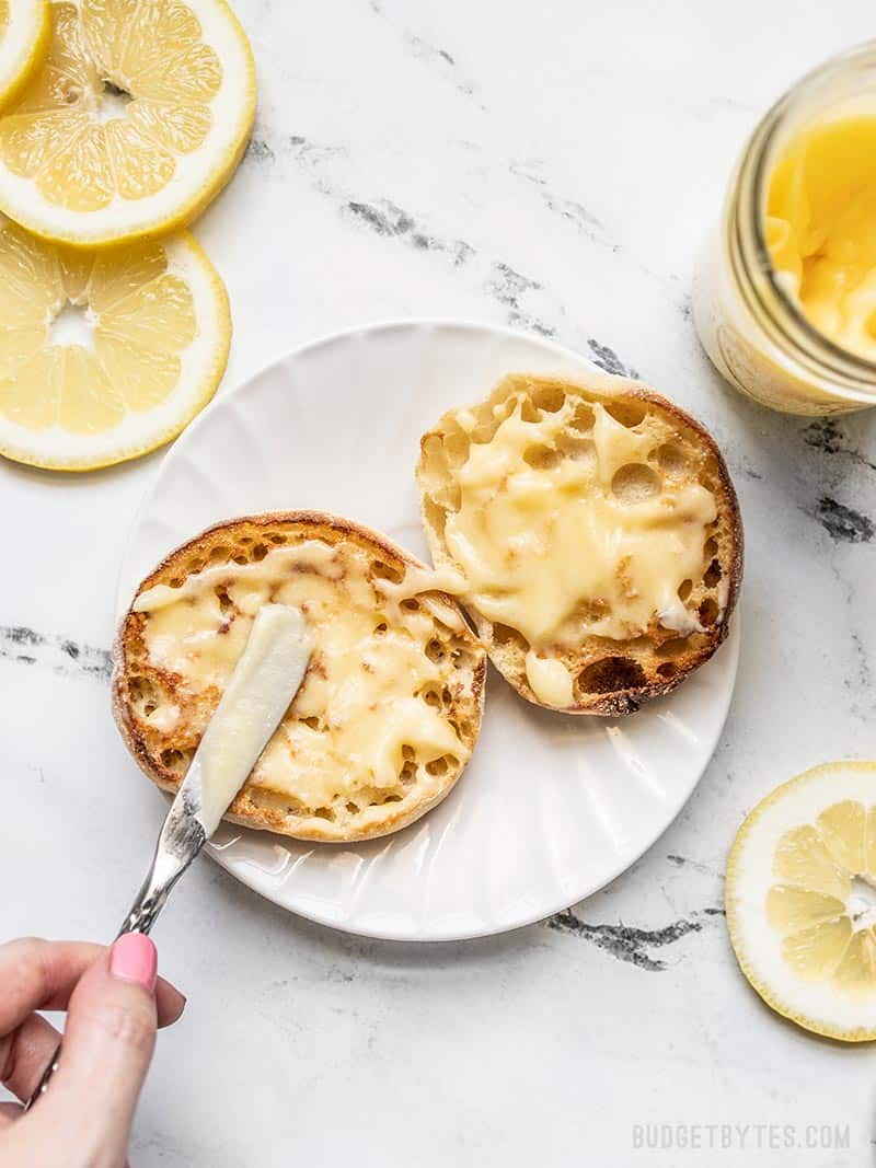 Lemon curd being spread onto a toasted english muffin, with the jar of curd and lemon slices on the sides.