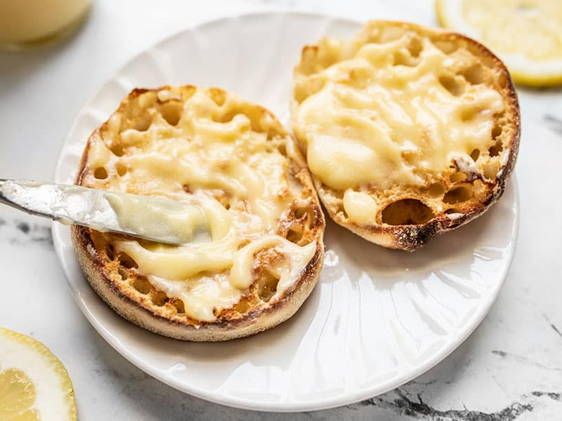Close up of lemon curd being spread onto a toasted english muffin