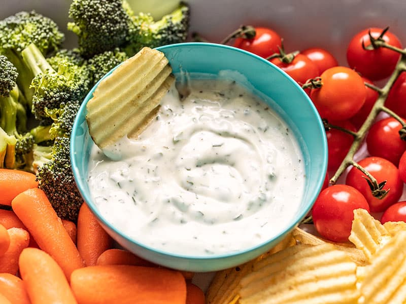 A chip sitting in a bowl of homemade ranch dip surrounded by vegetables and chips