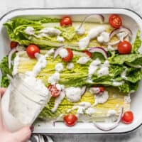 Homemade ranch dressing being poured onto a romaine salad with tomatoes and red onion