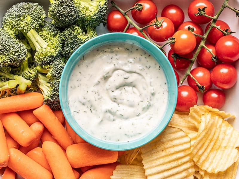 A bowl of homemade ranch dip in the middle of broccoli, tomatoes, carrots, and potato chips