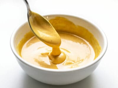 Honey Mustard Sauce dripping off a spoon into a bowl