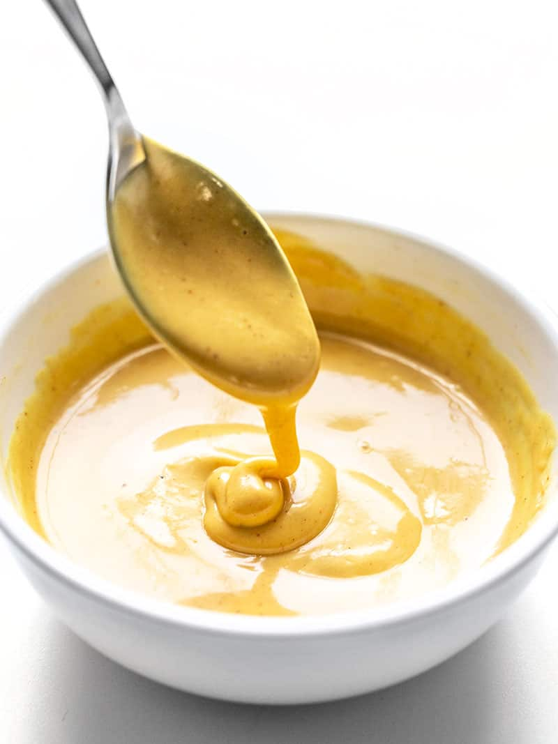 Honey Mustard Sauce dripping off a spoon into a white bowl.